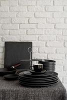 stack of black ceramic dishes and tableware on the table on white brick wall background photo