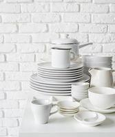 piles of white ceramic dishes and tableware on the table on white brick wall background photo