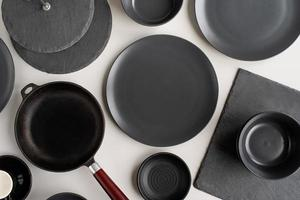 piles of black ceramic dishes and tableware top view on gray background photo