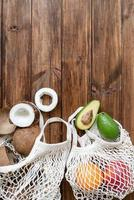 fresh tropical fruit in a mesh bag top view flat lay on wooden background photo