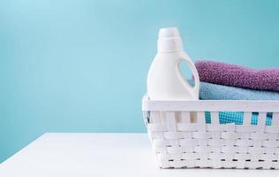 Cesta de lavandería con una botella de detergente y un montón de toallas limpias en el cuadro blanco aislado sobre fondo azul. foto