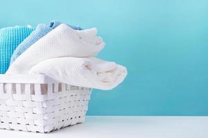 Pila de toallas limpias en una canasta de lavandería blanca sobre fondo azul. foto