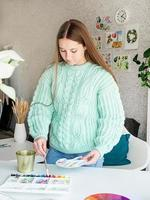 Young teenage woman artist holding color palette working in her studio photo
