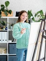 Young smiling woman artist holding color palette working in her studio photo
