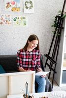 Beautiful woman artist painting a picture at home photo