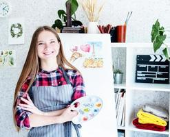 Young woman artist holding color palette working in her studio photo