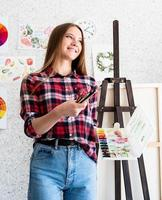 Beautiful woman artist in check shirt painting a picture at home photo