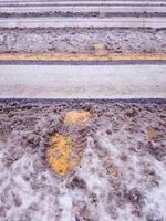 nieve sucia con huellas en la línea del paso de peatones. foto