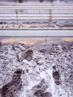 Paso de peatones nevado y resbaladizo con huellas. foto