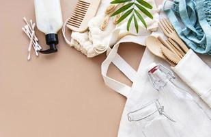 bolsas de algodón, bolsa de red con frascos de vidrio reutilizables, cubiertos de bambú y madera sobre fondo marrón. concepto de desperdicio cero. Respetuoso del medio ambiente. endecha plana foto
