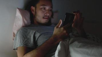 Young Asian men using a smartphone browsing web and scroll through social media feed on mobile phones. video