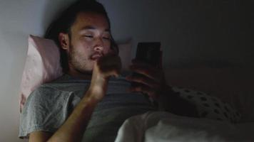 Asian men using a smartphone browsing web and scroll through social media feeds on mobile phones. video
