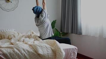 Asian man waking up and stretches while sitting on the bed in bedroom morning sun shines through the window at home. video