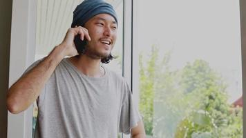 Asian businessman talking phone while standing beside the window in the living room at home. video