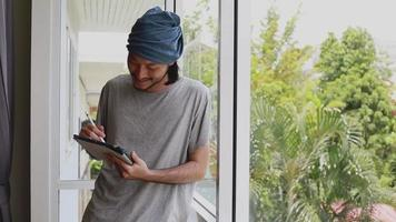 Asian man freelancer drawing on his tablet while standing beside the window in the office at home. video
