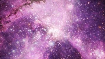 galaxy exploration through outer space towards beautiful glowing pink cloud nebula. video