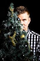 Stylish photo of a man hiding his face behind a christmas tree on a black background. Christmas and New Year concept