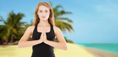 Young beautiful sporty woman doing yoga exercise on sea wooden beach near water. Girl practicing exercises mudra. Hands in namaste. Gratitude sign. Health summer concept photo