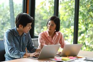 la nueva generación de hombres y mujeres jóvenes está sentada, consultando, trabajando y usando la computadora portátil en el escritorio de la oficina. foto