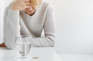 Elderly woman holding hand on her head. Selective focus on pills and glass of water. Headache and stress concept photo