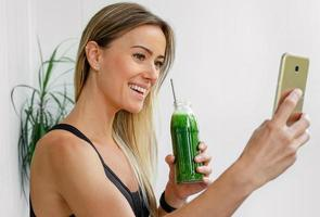 Cheerful sporty woman drinking green smoothie photo