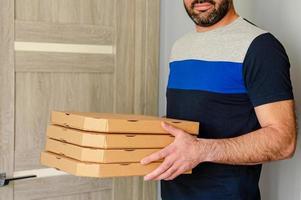hombre barbudo sosteniendo cajas de pizza en las manos. concepto de pedido y entrega de alimentos. foto