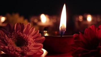 Happy Diwali. Burning diya oil lamps and flowers on dark background. Traditional celebration of the festival of light. video