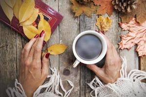 Hot coffee in the hands of a girl, a book with poems, autumn leaves, a knitted sweater on a wooden table background. Cozy autumn mood in October, November photo