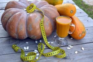 Diet vegetable juice. Huge pumpkin and zucchini on a wooden background. photo