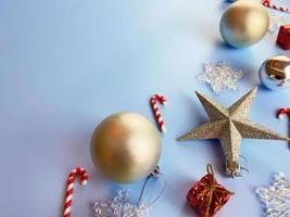 adornos navideños, caja de regalo, bolas doradas, copos de nieve sobre fondo azul. foto