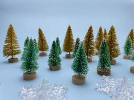 copos de nieve, pinos de color dorado y verde sobre fondo azul foto
