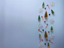 Vista superior de adornos navideños, pino, bolas rojas y doradas, copos de nieve sobre fondo azul. foto
