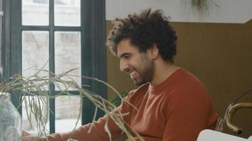Young Middle Eastern man sits at table watching laptop in front of him, laughs photo
