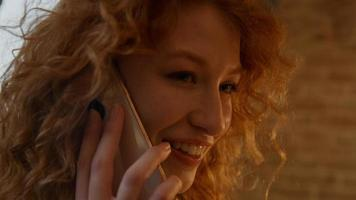 Close up of young white woman, calling with mobile phone, talking and smiling photo