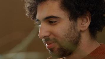 Close up of young Middle Eastern man, looks on laptop, smiles and talks photo