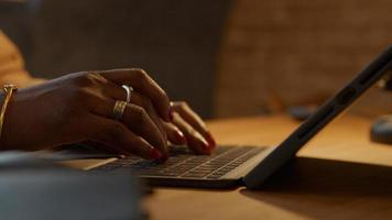 Close up of fingers of mature black woman typing on laptop photo