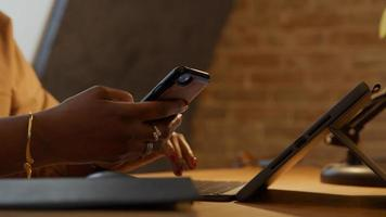 Close up of hands of mature black woman at table, typing on laptop and holding phone whilst talking photo