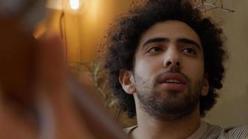 Headshot of young Middle Eastern man, talking to young mixed race woman who plays guitar photo