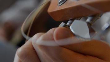 Close up of fingers of young mixed race woman, turning tuner of guitar, other hand touches string to tune photo