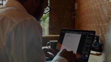 Black man wearing glasses, sitting at table, typing on laptop photo