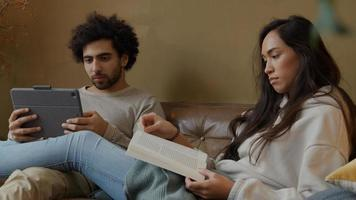 Young mixed race woman and young Middle Eastern man sitting on couch, woman reads book, man holds tablet, talking seriously photo