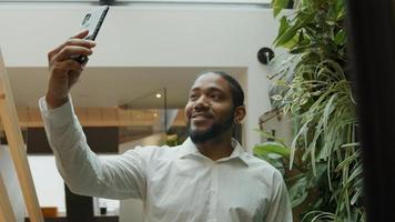 Black man standing, holding mobile phone in the air, following himself making video, smiling photo