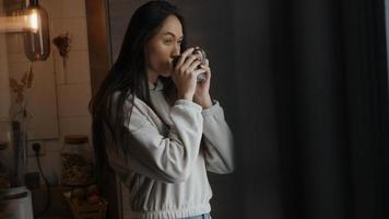 Young mixed race woman holds cup in hands, looking through window contemplatively photo