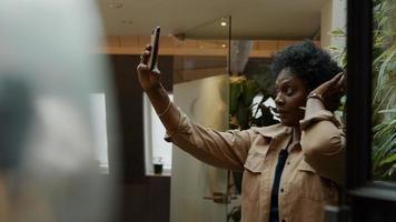 Black mature woman holds mobile phone in the air, adjusting her hair, looking at phone photo