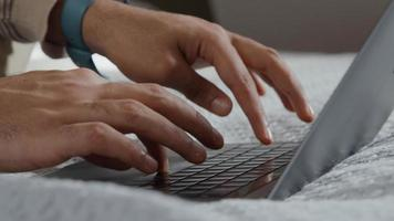 Close up of laptop on bed and hands of young Middle Eastern man, scrolling on touch pad and typing keyboard photo