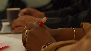 Close up of hands on table of black mature woman, holding pen photo