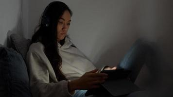 Young mixed race woman sits on couch in corner of living room, watching screen of tablet in front of her, reflection of screen on face and eyes photo