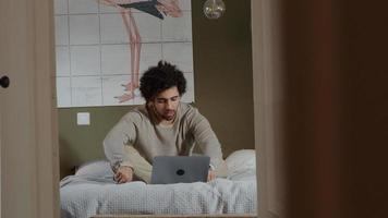 Joven de Oriente Medio se sienta en la cama, con una computadora portátil frente a él, conversando en línea, ajustándose el cabello y hablando foto