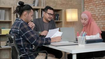 Young startup colleagues team who are Islamic people talk with their boss about financial projects working in an e-commerce business. Use laptop to online communication via Internet in a small office. video