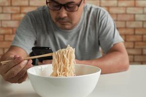 Un hombre asiático casual en el fondo de la pared de ladrillo leyendo un teléfono móvil usa palillos para comer fideos instantáneos calientes en una taza blanca durante la hora del almuerzo. estilo de vida de cocina tradicional asiática de comida rápida. foto